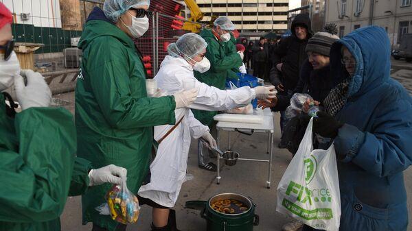 Волонтеры благотворительного фонда имени Елизаветы Глинки Доктор Лиза раздают еду бездомным в районе Ярославского вокзала