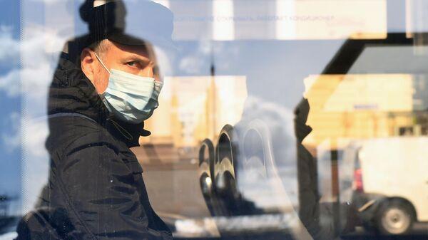 Пассажир в медицинской маске в салоне автобуса