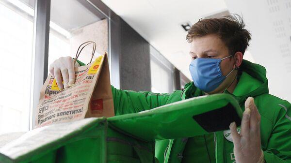 Курьер службы Delivery Club складывает в сумку заказ для жителя Москвы