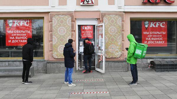 Покупатели и курьер службы доставки еды Delivery Club стоят в очереди у окна кафе KFC