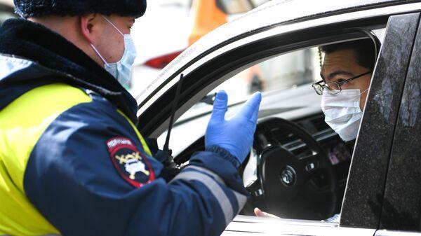Сотрудник дорожно-патрульной службы ГИБДД во время проверки документов у водителя в дни действия режима самоизоляции в Москве