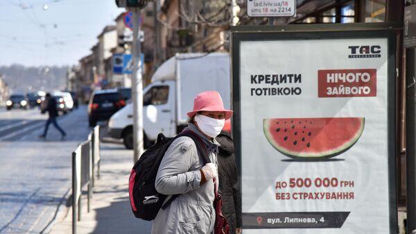 Женщина в защитной маске на одной из улиц во Львове