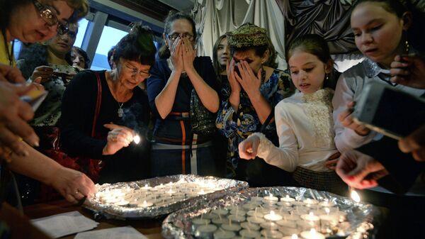 Женщины зажигают свечи в Новосибирском еврейском общинном культурном центре перед началом пасхального седера во время иудейского праздника Песах