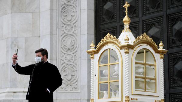 Священнослужитель в защитной маске после окончания Божественной литургии в храме Христа Спасителя в Москве