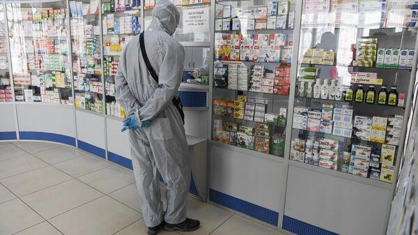 Человек в защитном костюме в одной из аптек Симферополя