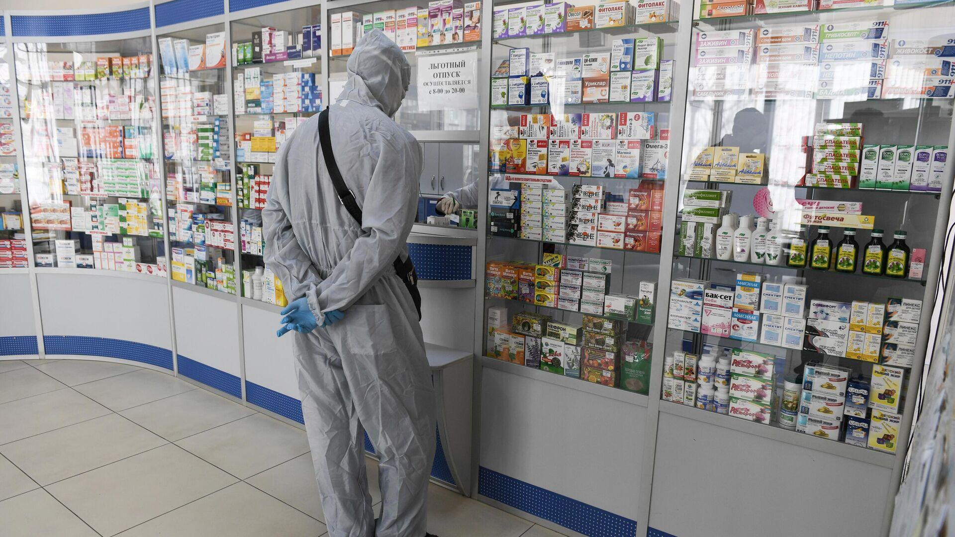 Человек в защитном костюме в одной из аптек Симферополя - РИА Новости, 1920, 15.09.2020