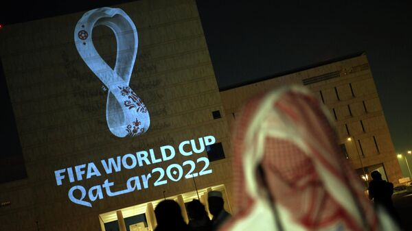 People gather at the capital Doha's traditional Souq Waqif market while the official logo of the FIFA World Cup Qatar 2022 is projected on the front of a building on September 3, 2019. (Photo by - / AFP)