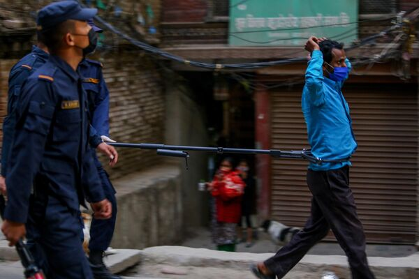 Полицейский во время задержания мужчины, нарушающего режим карантина, на одной из улиц Катманду, Непал