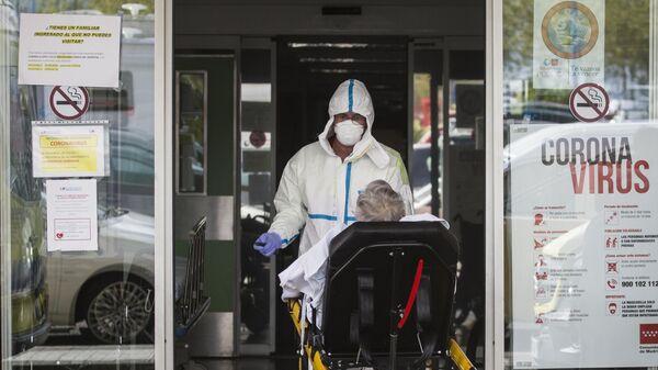 Медицинской работник доставляет пациента на каталке в приемное отделение госпиталя Северо Очоа в Мадриде