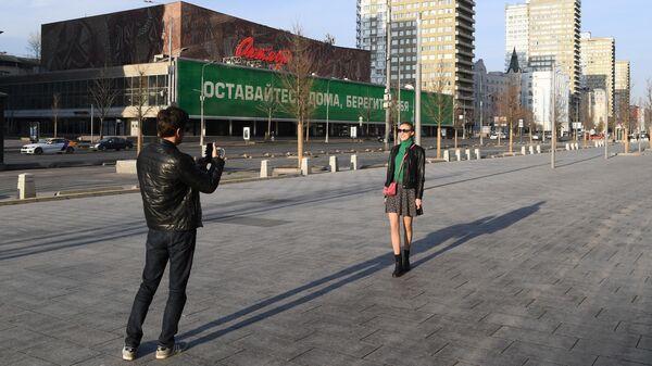 Молодые люди фотографируются на улице Новый Арбат в Москве