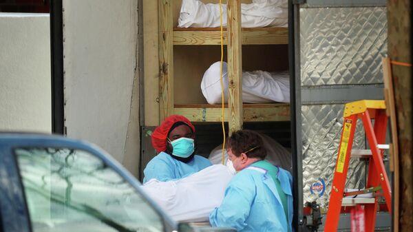 Медицинские работники транспортируют тело умершего человека в медицинском центре в Бруклине, Нью-Йорк