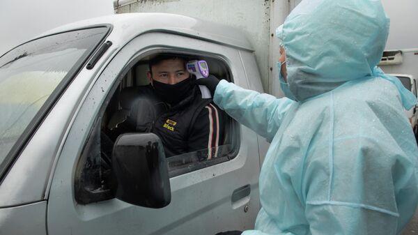 Медицинский работник проверяет температуру у водителя на блокпосте при въезде в Алма-Ату