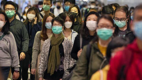 Пассажиры в медицинских масках в переходе метро Гонконга