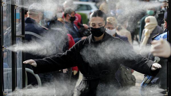 Люди проходят дезинфекцию перед выходом на рынок в Тиране, Албания