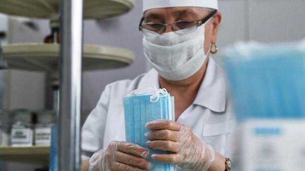 Сотрудница аптеки фасует одноразовые медицинские маски