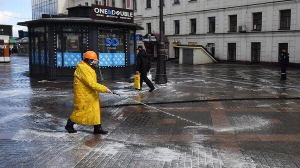 Сотрудник коммунальной службы проводит дезинфекцию тротуара у выхода со станции метро Комсомольская в Москве