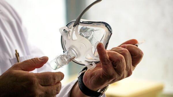 Врач держит в руках маску для искусственной вентиляции легких