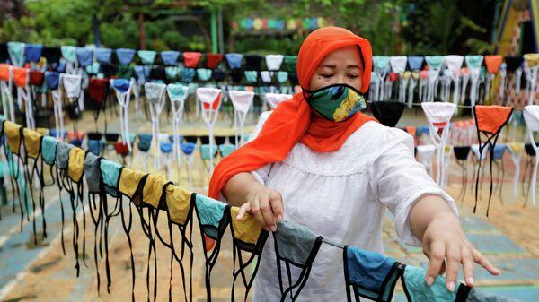 Женщина сушит тканевые маски для лица, прежде чем раздать их бесплатно по окрестностям в Тангеранге, на окраине Джакарты, Индонезия