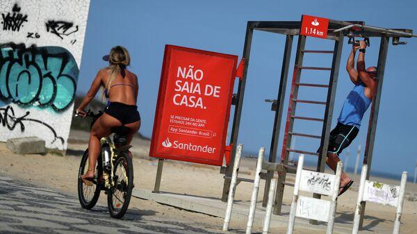 Девушка проезжает мимо баннера Не выходи из дома на пляже Ипанема в Рио-де-Жанейро во время пандемии коронавируса