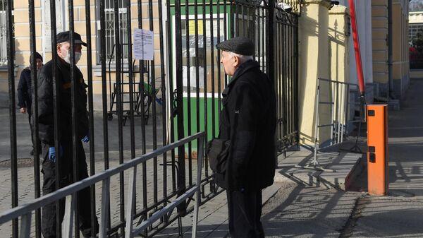 Мужчина читает объявление на воротах Ваганьковского кладбища в Москве
