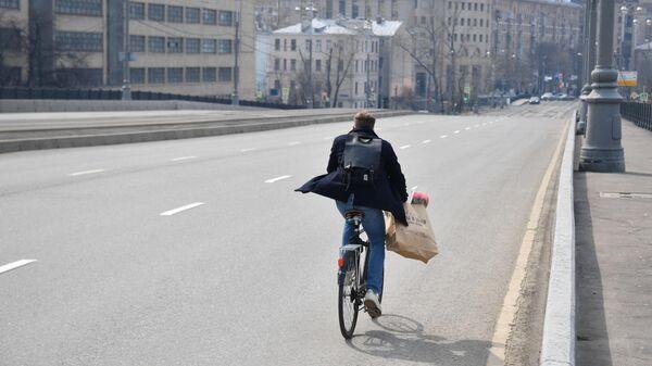 Велосипедист едет по улице в Москве