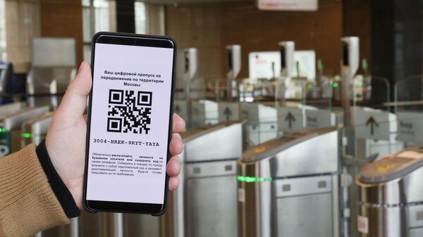 Житель Москвы демонстрирует цифровой пропуск для передвижения по городу, оформленный через сайт мэра и правительства Москвы