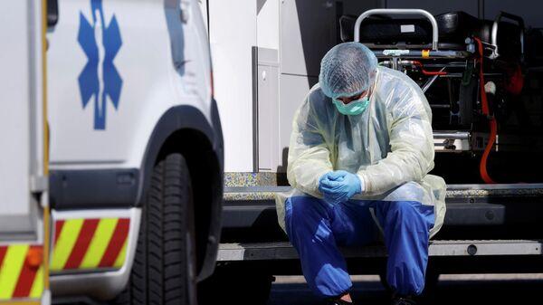 Медицинский работник возле машины скорой помощи в Страсбурге, Франция