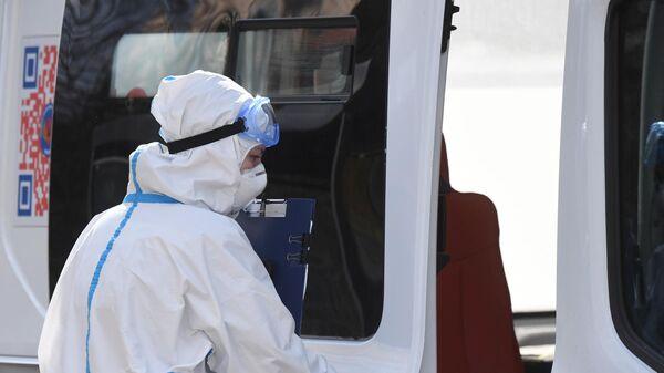 Медицинский работник возле автомобиля скорой помощи у здания ФМБА в Химках