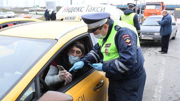 Сотрудник ДПС ГИБДД проверяет электронный пропуск у водителя такси при въезде в Москву