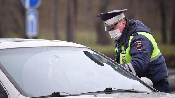 Сотрудник ДПС ГИБДД проверяет документы у водителя