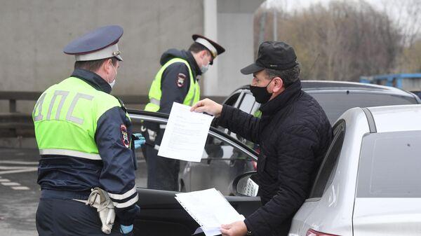 Сотрудники ГИБДД во время проверки электронных пропусков у водителей на блокпосту при въезде в Москву