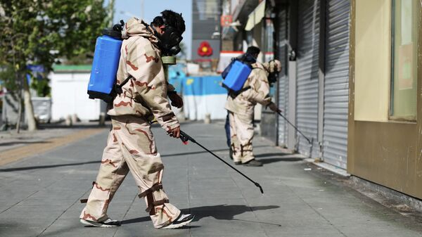 Волонтеры в защитных костюмах дезинфицируют улицы в Тегеране, Иран