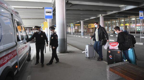 Сотрудники полиции и пассажиры, прибывшие рейсом компании Аэрофлот из Нью-Йорка, в Международном аэропорту Шереметьево