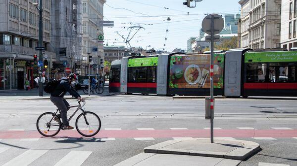 Мужчина в маске едет на велосипеде в Вене