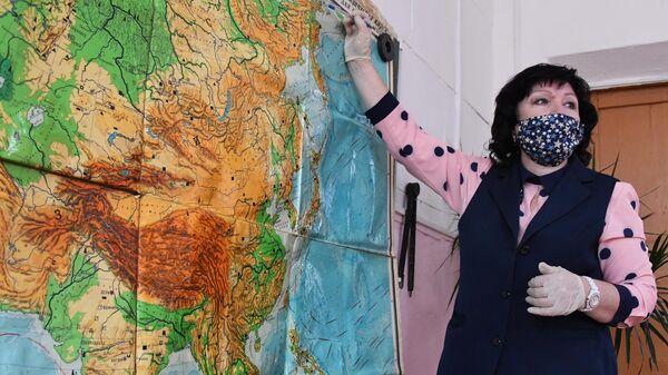 Учитель в защитной маске ведет урок в общеобразовательной школе №8 в селе Нежино Приморского края
