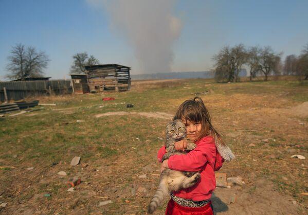 Девочка с котом во дворе частного дома в селе Раговка. Лесной пожар, возникший в районе села Полесское на территории зоны отчуждения Чернобыльской АЭС на Украине