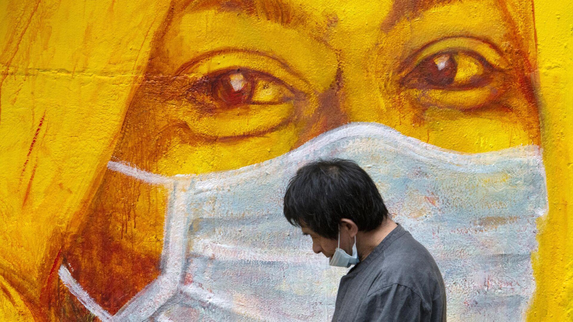 Прохожий около стены с изображением человека в маске в Гонконге - РИА Новости, 1920, 02.10.2020