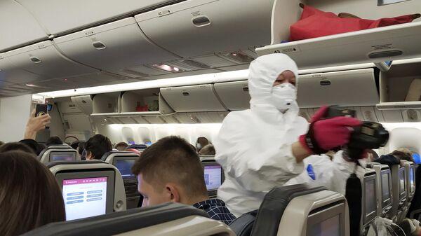 Сотрудник медицинской службы измеряет температуру у граждан России, прилетевших рейсом авиакомпании Россия