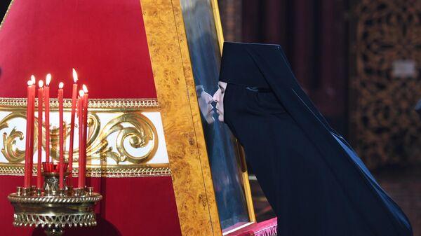 Монахиня целует икону в храме Христа Спасителя в Москве во время праздничного пасхального богослужения