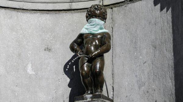 Статуя Писающий мальчик в защитной маске во время вспышки коронавирусной инфекции (COVID-19) в Брюсселе
