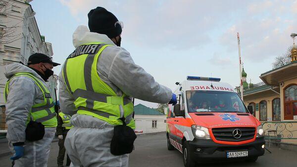 Сотрудники полиции и автомобиль скорой помощи в Киеве