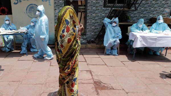 Женщина ждет своей очереди на бесплатное медицинское обследование в Дхарави, одних из крупнейших трущоб в Азии, Мумбаи, Индия