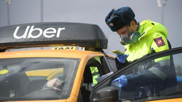 Инспектор дорожно-патрульной службы проверяет у водителя цифровой пропуск