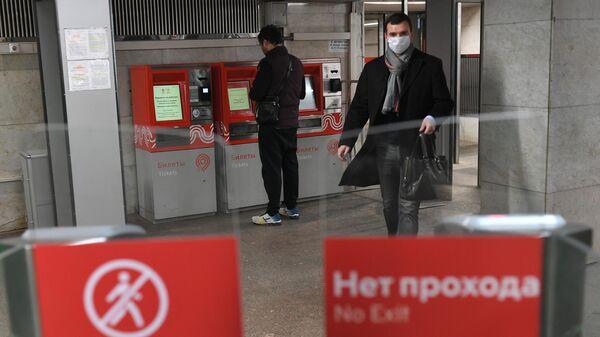 Пассажир у турникета на станции метро Сходненская в Москве