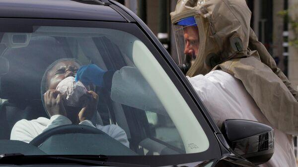 Мединский работник берет мазок для проведения анализа на коронавирус в больнице в Сомервилле