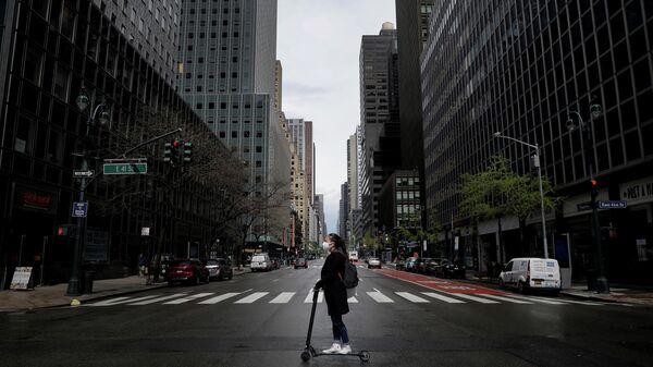 Девушка в защитной маске едет на самокате по улице в Нью-Йорке