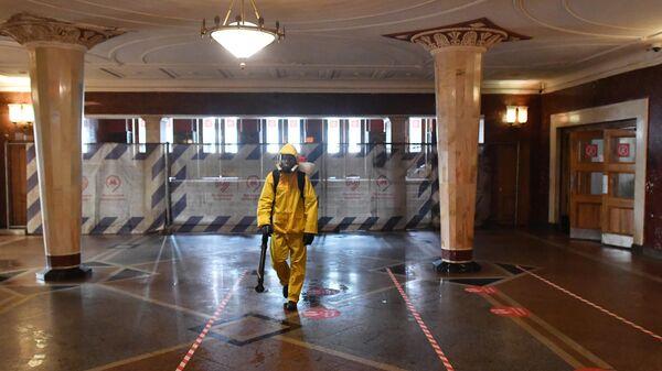 Сотрудник МЧС РФ проводит дезинфекцию в вестибюле станции метро Киевская в Москве