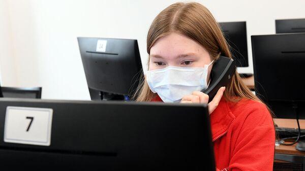 Сотрудница колл-центра в штабе волонтеров общается по телефону