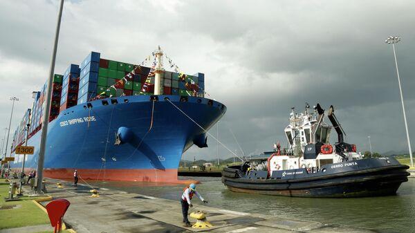 Работник Панамского канала стыкует китайский контейнеровоз Cosco