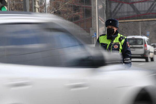 Инспектор дорожно-патрульной службы во время проверки наличия цифрового пропуска на передвижение по Москве